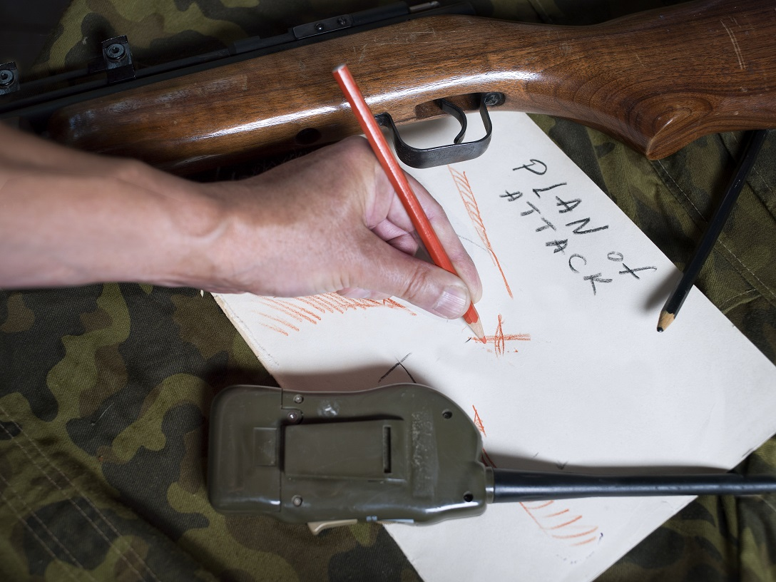 Male hand with pencil planning an abstract attack on a piece of paper, a gun and radio laid on a camouflage uniform. Closeup studio shot