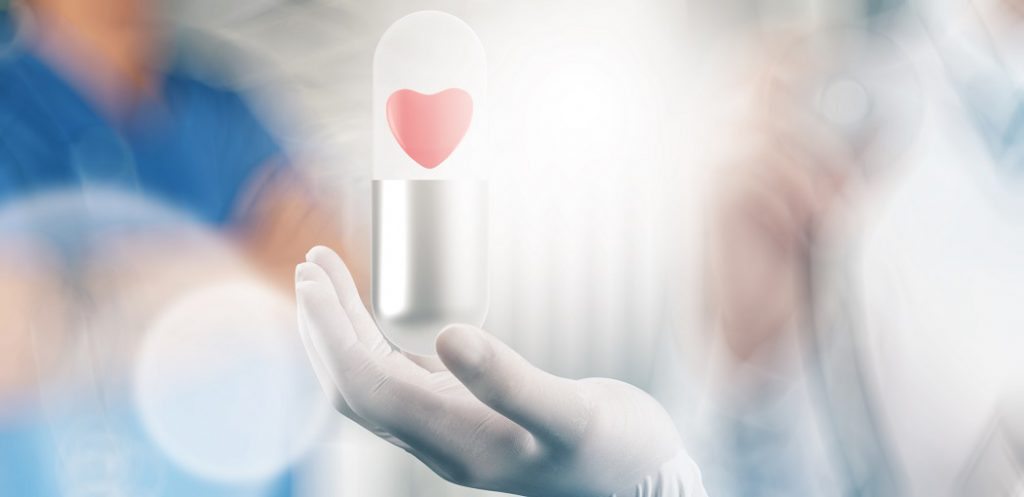 medical hand with glove heart inside capsule pill as concept