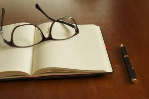 Reading glasses and schedule book and pen